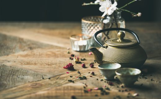 Traditional Asian tea ceremony arrangement. Golden iron teapot, cups, candles and almond blossom flowers over vintage wooden table background, copy space, selective focus